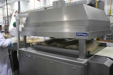 Conveyor-belt-fed vacuum packaging of full loins.